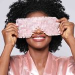 Modelo segurando Máscara de Quartzo Rosa Rose Quartz Eye Mask aberta frente