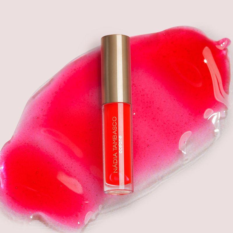 brilho labial nádia tambasco astral na cor vermelho com embalagem fechada e textura ao fundo