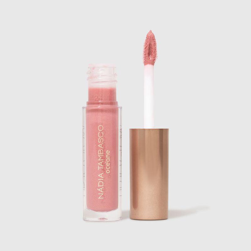 brilho labial nádia tambasco obsession na cor rosa cintilante com embalagem aberta e aplicador ao lado direito