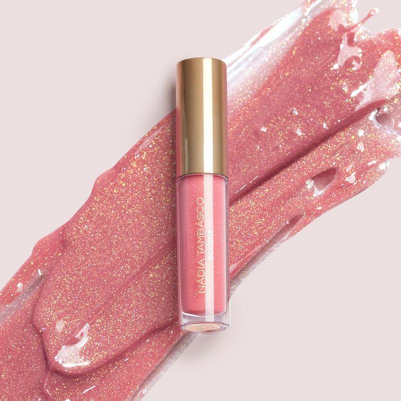 brilho labial nádia tambasco obsession na cor rosa cintilante com embalagem fechada e textura ao fundo