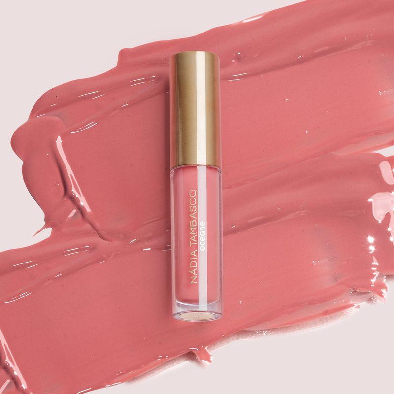 brilho labial nádia tambasco luxe na cor rosa com embalagem fechada e textura ao fundo