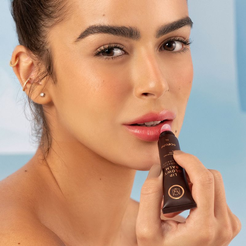 Mariana Saad aplicando o produto reparador de lábios mariana saad by océane lip glowy balm nos lábios