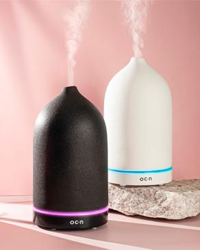 Banner ambiente difusor Océane, a foto mostra um difusor de aromas preto e um difusor de aromas branco.